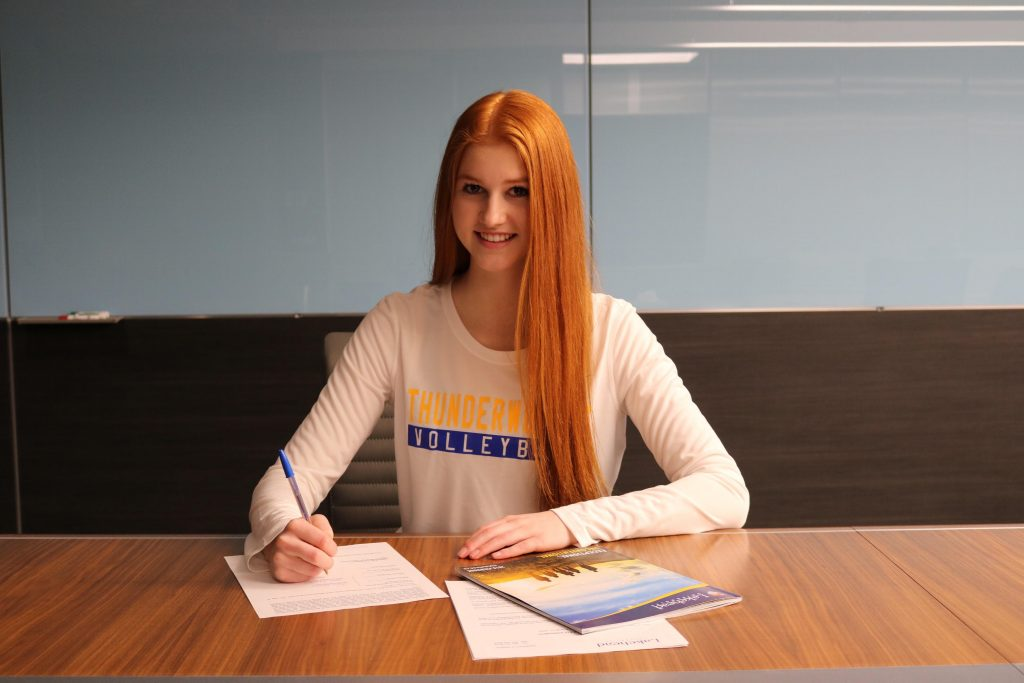 Tori Dauvin signs her Thunderwolves women's volleyball commitment papers,